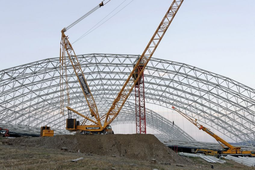 A 500-metric-ton crawler crane erecting the arched hall, which appears very delicate from a distance